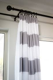 interior grey and white fabric striped shower curtain on black hook connected by beige wall