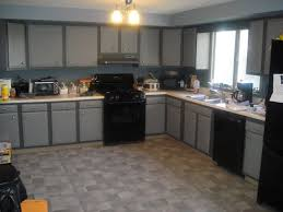 l shaped grey wooden kitchen cabinet having white countertop on