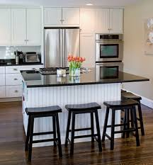 kitchen with white shaker cabinets beadboard backing on island black marble countertop and black