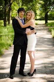 young couple of high school seniors after the prom in a summer stock photo young couple of high school seniors after the prom in a summer park