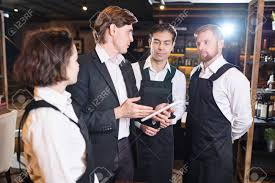 Confident Restaurant Manager Discussing Seating Chart With Waiter