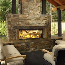 luxury outdoor wood burning fireplace with natural stone chimney and clear glass cover and outdoor living space