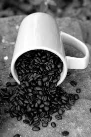 Spill the Beans - fine art black and white photography - a cup full of  coffee beans spilling onto the ground.