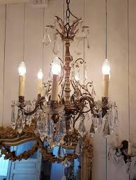 french chandelier made of bronze and crystal drops and crystal bobeche cups looks very delicate