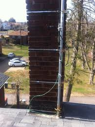 close up photo of lower tv antenna mast chimney straps and grounding clamps