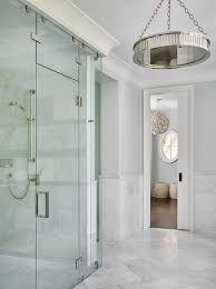 steam shower kit. Large Marble Herringbone Floor Tiles, Accenting Gray Half Tiled Bathroom Walls, Lead To A Seamless Glass Steam Shower Fitted With Polished Nickel Kit