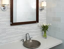 mirror with dark brown wooden frame between lamps plus gray long vanity and round gray sink