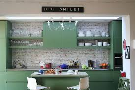 pastel green island with granite countertop white bar stools whitewashed brick wall and colorful cabinets for the stylish modern kitchen