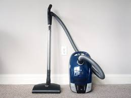 Upgrade pick vacuum cleaner standing on a household carpet against a wall.