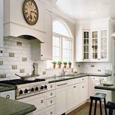 White painted kitchen cabinets Diy Whitepainted Cabinets Make This Kitchen Feel Bright Light And Open Greenhued Granite Countertops And Randomly Spaced Decorative Backsplash Tiles Add Bob Vila Painted Kitchen Cabinets 14 Reasons To Transform Yours Bob Vila