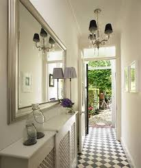 Narrow hallway lighting ideas Corerp Narrow Hallway Lighting Ideas With Beautiful Chandelier And Wall Mounted Wide Mirror Featuring White Wall Paint Combine With Geometric Flooring Creative Design Decoration Room Furniture Decoration Narrow Hallway Lighting Ideas With Beautiful Chandelier