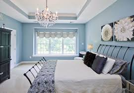 beautiful blue bedroom with white tray ceiling hanging chandelier and artwork