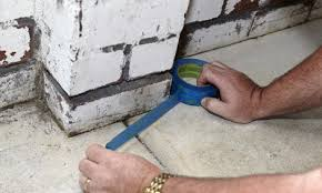 person putting masking tape on walls