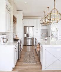 white kitchen, large gold light fixtures in kitchen, painted brick ...