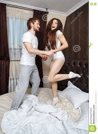 Married Couple Jumping On Bed