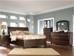 light colored wood furniture dark brown wood bedroom furniture with dark smokey blue walls white bedding dark wood floor a light brown rug white curtains on