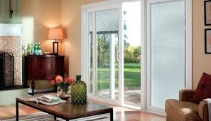windows with blinds inside living room with sliding patio door and blinds between the glass blinds