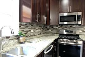 contemporary kitchen with glass mosaic and dark cabinets backsplash white countertops granite