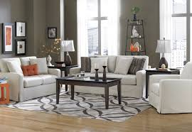 what size area rug for living room mixed with laminate floor and clean white fabric upholstery sofa also twi small candles over black rectangle wooden table