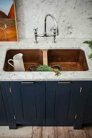 a gorgeous double copper sink in a white stone countertop look chic especially with a