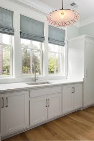 eye catching white cottage style laundry room with light gray shaker cabinets nickel pulls and corian countertops