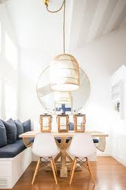 hung from a vaulted ceiling in fron tof a round gold mirror a basket pendant light illuminates a square trestle dining table topped with three wood and