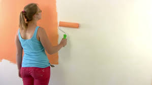 girl paints a wall in orange with a paint roller at the end puts