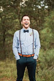 picture of dark teal pants a blue printed shirt a black bow tie brown suspenders and an amber leather belt ffor a stylish and simple look