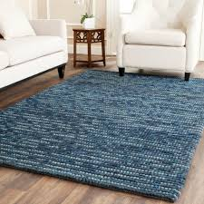alluring wool jute rug in navy blue on wood flooring living room design completed with deluxe white sofa and armchair also side wooden table potted plant