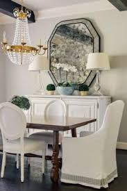 a white sideboard and dining chairs are striking against walls painted pratt lambert paints woodwitch in this dining room by paloma contreras