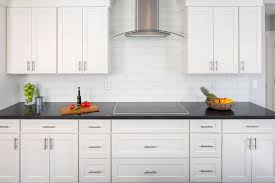 stainless and glass range hood shown mounted next to cliqstudios dayton painted white cabinets