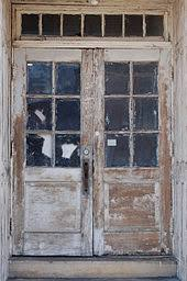 old double french doors 6 lites each with hinges on the exterior they must open outward it is uncertain whether there is a central mullion