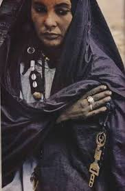 Algeria  August      Hands gleaming darkly with the indigo dye that colours her robe  a woman of the Tuareg  wandering Berbers of the Sahara  clasps her