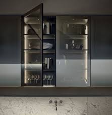 a kitchen cabinet with smoke glass doors shows off the glasses and dishes but gently