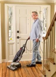Man Vacuuming Hardwood Floor With Kirby Upright Vacuum