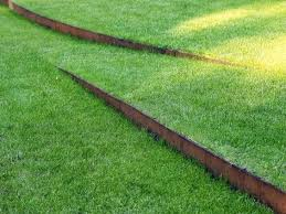 is your lawn sloped and difficult to work with give it a natural gentle flow by using cor ten steel to make a descending pathway