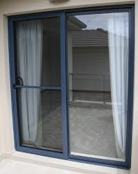 high glass sliding doors with gray wooden frame completed with white curtains
