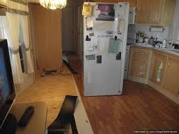 moving the refrigerator onto the installed laminate flooring in the kitchen