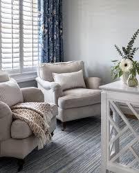 beige roll arm chairs on blue stripe rug
