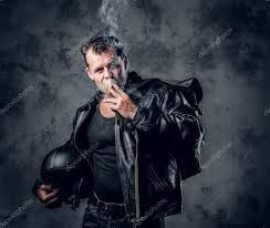 a man in leather jacket holds motorcycle helmet and smoking a cigarette photo by fxquadro