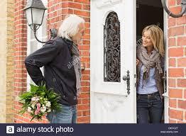 opening front door. Senior Man With Bouquet, Mid Adult Woman Opening Front Door