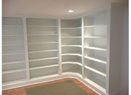 white painted wooden built it corner shelves which prettify with ceiling light with bookcase