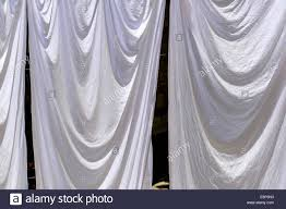 hanging sheet white bedding sheets hanging to dry on a washing line stock photo