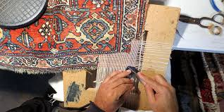 one of our rug reweavers working on a persian rug repair