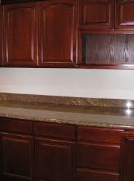 dark brown color staining oak kitchen cabinets with marble countertop ideas and white wall interior color decorating ideas