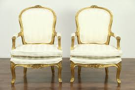 pair of carved french style chairs deep gold finish