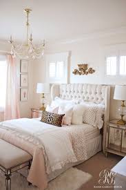 Pink and gold bedroom featuring tufted wingback headboard by Randi Garrett  Design