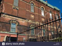 Old brick building with wrought iron fence in Saint John New Stock