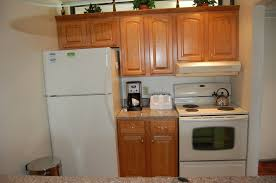 white fridge in kitchen. kitchen brown wooden cabinet with marble countertop and white metal stove fridge on wall paint inspiring ideas of prefab cabinets in