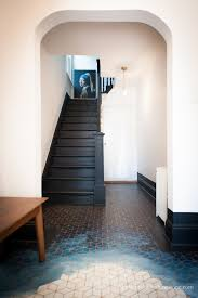 a dramatic hallway makeover is completed on a small budget including an original hand painted floor some modern accents and white walls